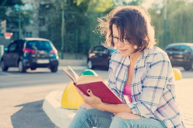 Portrait en plein air de femme mature dans des verres avec un livre.