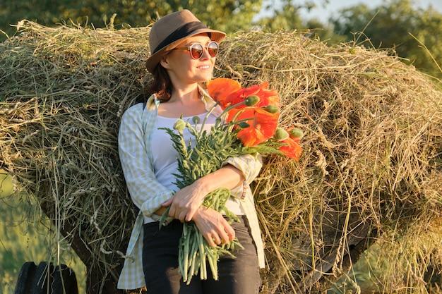 Portrait en plein air d'une femme mature heureuse avec bouquet de fleurs de coquelicots rouges.