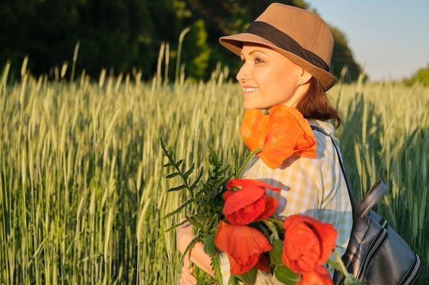 Portrait en plein air de femme mature heureuse avec des bouquets de fleurs de coquelicots rouges