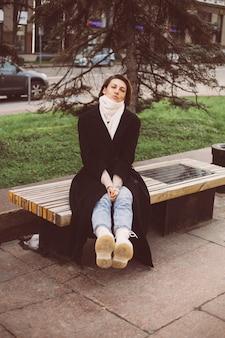 Portrait en plein air de femme de race blanche portant manteau d'hiver noir et écharpe assis sur un banc, ville sur fond