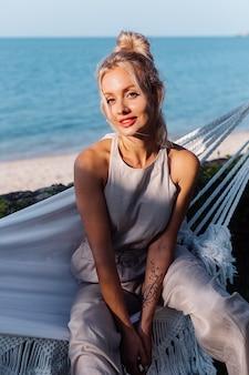 Portrait en plein air de femme de race blanche riche en combinaison classique avec rouge à lèvres par hamac en vacances à l'extérieur de l'hôtel villa