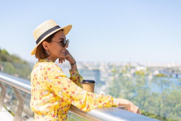 Portrait en plein air de femme en robe d'été jaune et chapeau avec tasse de café en profitant du soleil, se dresse sur le pont avec vue imprenable sur la ville