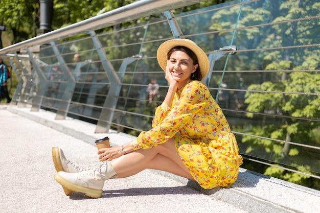 Portrait en plein air de femme en robe d'été jaune et chapeau avec tasse de café en profitant du soleil