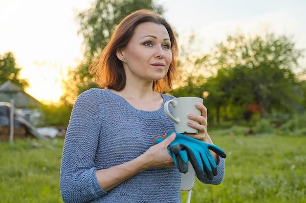 Portrait en plein air de femme avec tasse de thé, femme avec des gants au repos