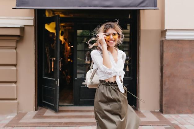 Portrait en plein air de fille inspirée de rire avec des boucles blondes en agitant tenant des lunettes jaunes