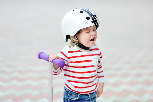 Portrait en plein air d'un garçon en bas âge qui pleure dans un casque de protection avec scooter