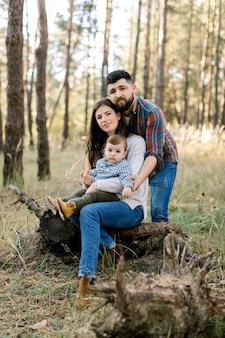 Portrait en plein air de l'heureuse famille caucasienne élégante dans des vêtements décontractés, de jeunes parents et de mignon petit fils enfant, sur une promenade dans une belle forêt de pins, assis sur un journal de vieil arbre et regardant la caméra