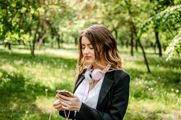 Portrait en plein air de jeune femme d'affaires dans les écouteurs