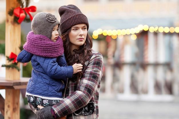 Portrait en plein air de jeune femme et petite fille à la décoration de noël en ville