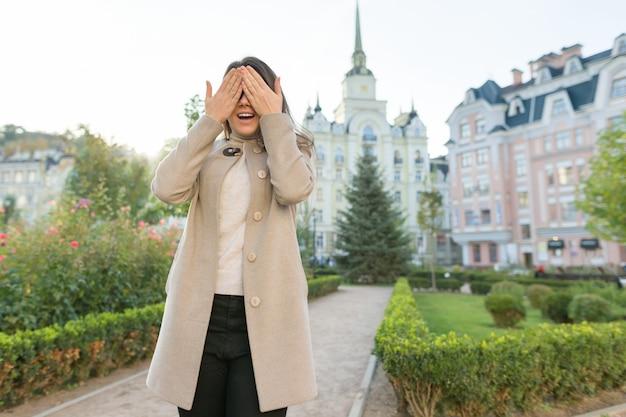 Portrait en plein air de jeune femme qui couvre ses yeux
