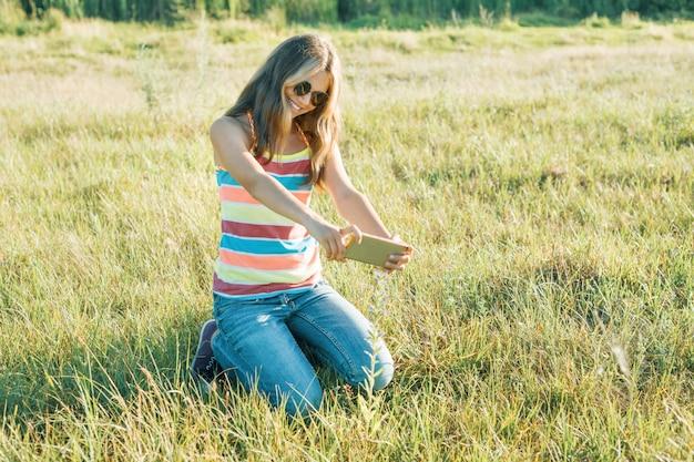 Portrait en plein air de jeune fille adolescente à l'aide de smartphone
