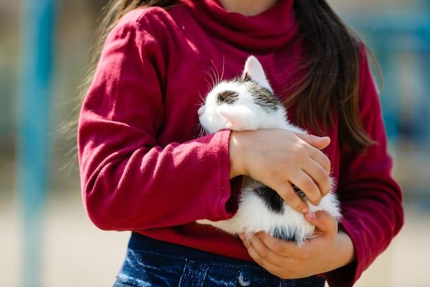 Portrait en plein air de jeune fille enfant avec petit chaton, fille jouant avec un chat naturel