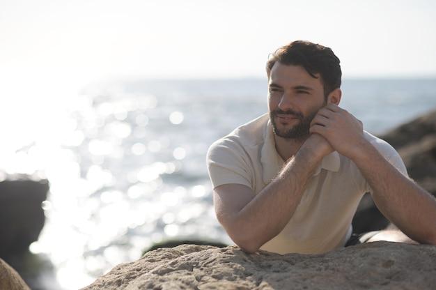Portrait en plein air de jeune homme au repos élégant près de la mer