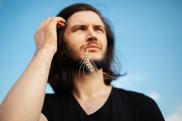 Portrait en plein air de jeune homme aux cheveux longs avec épi de blé dans la bouche.