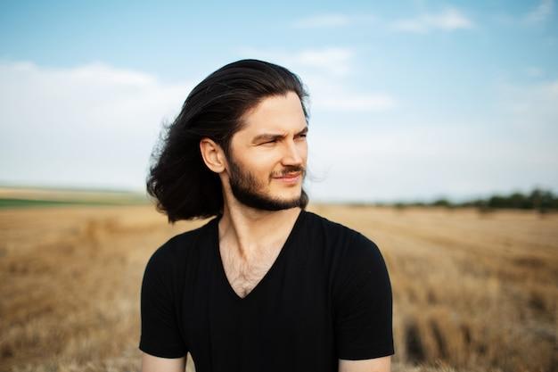 Portrait en plein air d'un jeune homme aux cheveux longs, sur fond de champ de blé.
