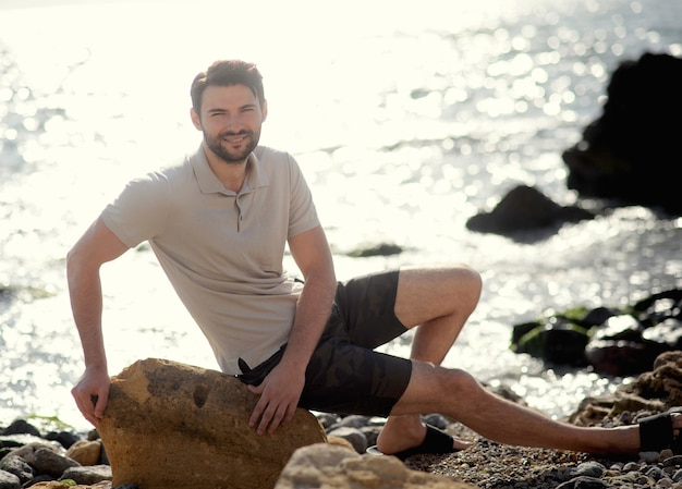 Portrait en plein air de jeune homme élégant, polo blanc, assis sur une pierre