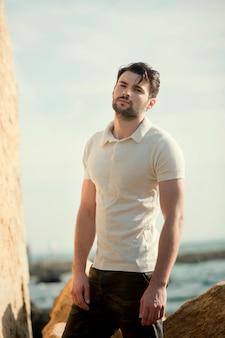 Portrait en plein air de jeune homme élégant, polo blanc