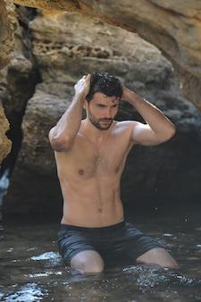 Portrait en plein air de jeune homme élégant près de la mer et des rochers, seins nus