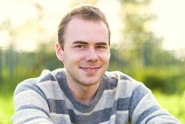 Portrait en plein air d'un jeune homme heureux, sourit avec bonheur.