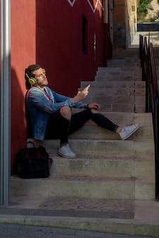 Portrait en plein air de jeune homme moderne avec un téléphone intelligent assis dans la rue.