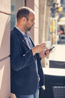 Portrait en plein air de jeune homme moderne avec téléphone portable dans la rue.
