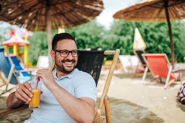 Portrait en plein air d'un jeune homme souriant sur la plage. boire un cocktail en étant assis sur une chaise de plage.