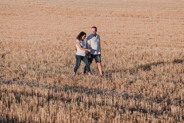 Portrait en plein air d'un jeune jeune couple enceinte marchant dans un champ jaune. mode de vie de famille en plein air.