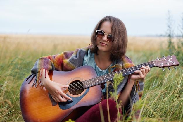 Portrait en plein air de jolie femme aux cheveux noirs portant des lunettes de soleil jouant de la guitare acoustique démontrant son talent ayant une expression réfléchie