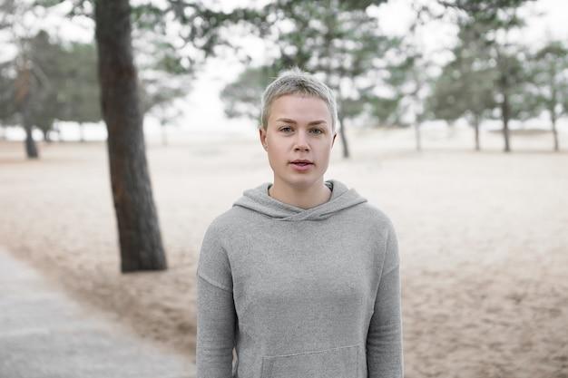 Portrait en plein air de jolie femme blonde aux cheveux courts à la mode portant un sweat à capuche gris à la mode reprenant son souffle pendant le repos tout en courant dans le parc seul, travaillant sur l'endurance et la force