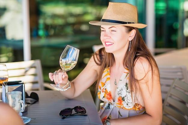 Portrait en plein air d'une jolie femme touristique en chapeau de paille dégustation et boire du vin blanc dans un café ou un restaurant de rue