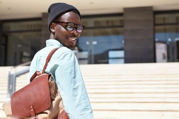 Portrait en plein air de joyeux jeune écrivain masculin se dépêchant de bâtiment moderne pour entretien d'embauche