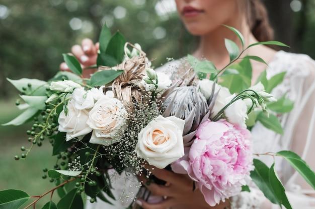 Portrait en plein air de la mariée dans un peignoir en dentelle blanche tient dans ses mains un bouquet de mariage avec des roses