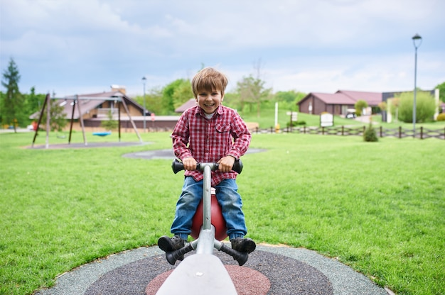Portrait en plein air de mignon garçon d'âge préscolaire en riant se balançant sur une balançoire à l'aire de jeux