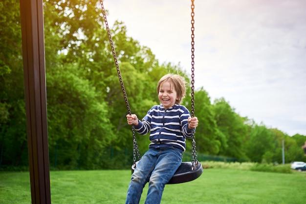 Portrait en plein air de mignon garçon d'âge préscolaire rire garçon se balançant sur une balançoire à l'aire de jeux