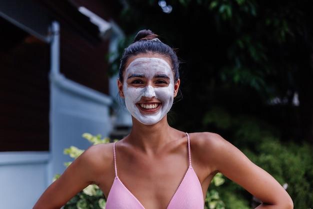 Portrait en plein air de la peau bronzée calme jolie femme caucasienne en bikini au spa avec masque peeling blanc sur le visage