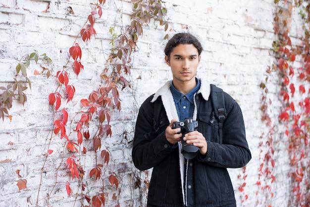 Portrait en plein air d'un photographe masculin debout près d'un mur de fond blanc tenant un appareil photo reflex numérique, regardant la caméra