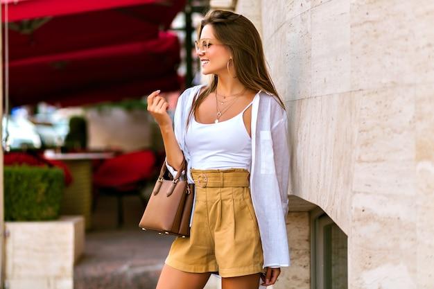 Portrait en plein air d'un superbe mannequin brune bronzée mince portant un short en lin beige, un sac de luxe en cuir caramel, une chemise blanche et des accessoires dorés, se promenant dans les rues de paris.