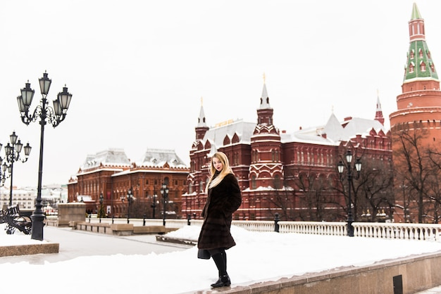 Portrait en pleine croissance, belle femme russe dans un manteau de vison sur la place rouge à moscou à noël