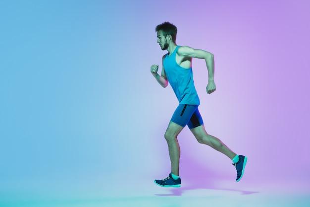 Portrait de pleine longueur active jeune caucasien courir, faire du jogging homme sur gradient studio en néon