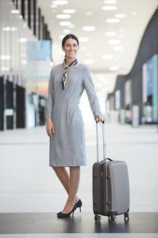 Portrait de pleine longueur d'agent de bord élégant et souriant tout en posant avec valise à l'aéroport
