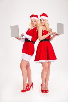 Portrait de pleine longueur de deux femmes heureuses en tissu santa à l'aide d'un ordinateur portable isolé sur fond blanc