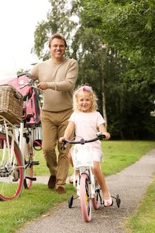 Portrait de pleine longueur du père et de la fille faisant du vélo ensemble dans le parc