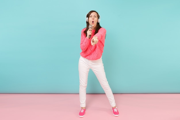 Portrait de pleine longueur femme amusante en pull tricoté, pantalon blanc, casque chantant une chanson dans un microphone