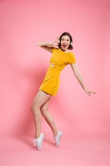 Portrait de pleine longueur de femme charmante heureuse dans les écouteurs debout sur les orteils