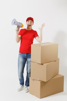 Portrait de pleine longueur de femme de livraison en casquette rouge, t-shirt isolé sur fond blanc. courrier féminin criant dans un mégaphone près de boîtes en carton vides. réception du colis. copiez la publicité de l'espace.