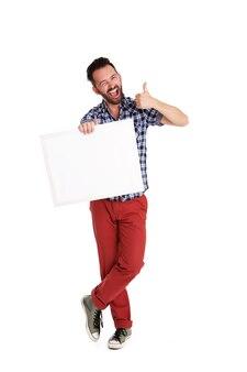 Portrait de pleine longueur d'homme gai tenant une affiche vide et montrant les pouces vers le haut sur blanc b