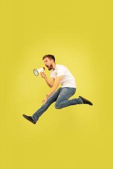 Portrait de pleine longueur d'homme sautant heureux isolé sur fond jaune. modèle masculin de race blanche dans des vêtements décontractés. liberté de choix, inspiration, concept d'émotions humaines. appeler avec la paix de la bouche.