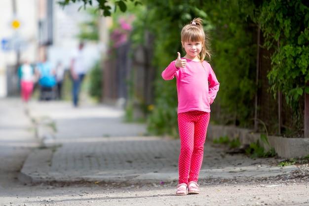 Portrait de pleine longueur de jolie petite fille en vêtements de sport roses et longue queue de cheval blonde souriante à la caméra avec le geste du pouce levé