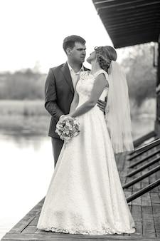 Portrait de pleine longueur noir et blanc de l'heureuse mariée et le marié posant sur la jetée de la rivière