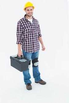 Portrait de pleine longueur de réparateur mâle heureux avec boîte à outils sur fond blanc
